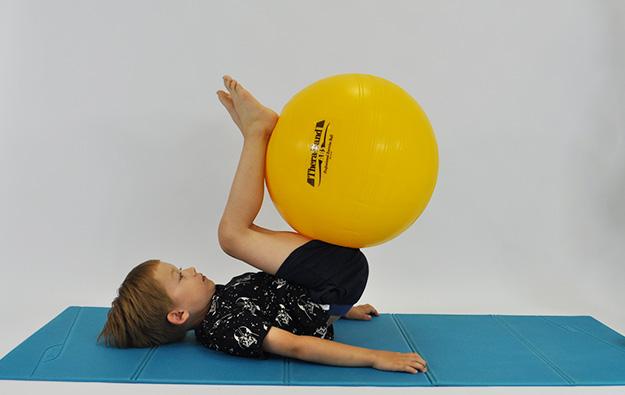 dziecko w leżeniu tyłem, nogi leża na piłce, odrywa nogi razem z piłka i przyciąga do brzucha