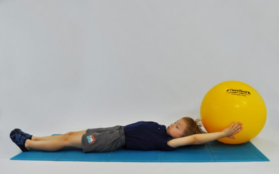 ćwiczenia na mięsnie brzucha. Dziecko leży na plecach, kończyny dolne wyprostowane, ręce zgięte w stawach barkowych trzymają piłkę