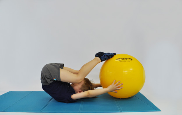 dziecko w leżeniu tyłem ciągnie nogi za głowę dotykając nimi piłkę którą trzyma w rękach