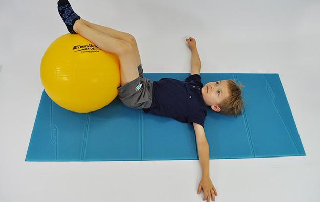 dziecko w leżeniu tyłem nogi trzyma na piłce, napina brzuch i skręca kolana z piłką w obie strony