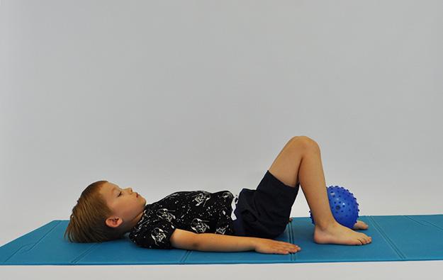 ćwiczenia na mięsnie brzucha. Dziecko leży na plecach, kolana ugięte, stopy oparte na podłodze, między stopami piłka