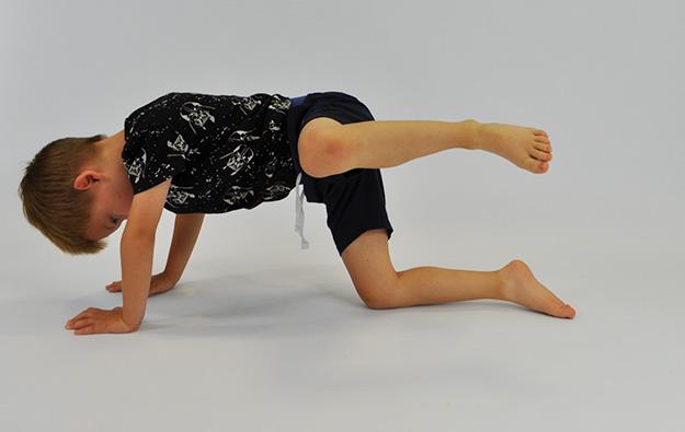 dziecko w klęku podpartym unosi zgięta nogę w bok