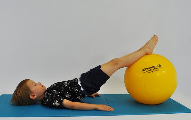 dziecko w leżeniu tyłem nogi na piłce unosi pośladki