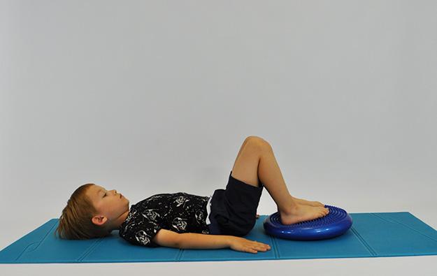 ćwiczenia na pośladki. Dziecko leży tyłem nogi ugięte na poduszce sensorycznej