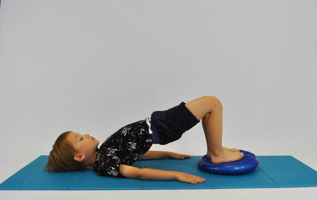 dziecko w leżeniu tyłem kolana ugięte, stopy napo duszce sensorycznej, unosi biodra