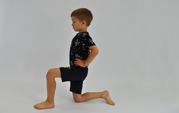 ćwiczenie rozciągające staw biodrowy. Dziecko klęczy na jednej nodze, ręce na biodrach