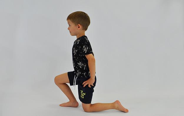 ćwiczenie rozciągające staw biodrowy. Dziecko klęczy na jednej nodze, ręce na biodrach, dziecko idzie miednicą w przód rozciągając biodro nogi opartej na kolanie