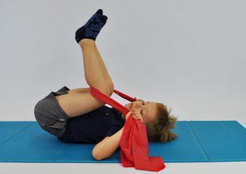 ćwiczenia rozciągające kręgosłup lędźwiowy. Dziecko leży na plecach w rękach trzyma taśmę elastyczną zaczepioną pod kolanami. Dziecko przyciąga kolana w raz z taśmą do klatki piersiowej
