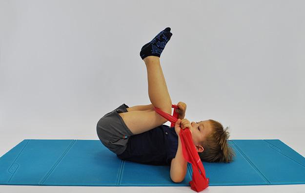 ćwiczenia rozciągające kręgosłup lędźwiowy. Dziecko leży na plecach w rekach trzyma taśmę elastyczna zaczepiona pod kolanami