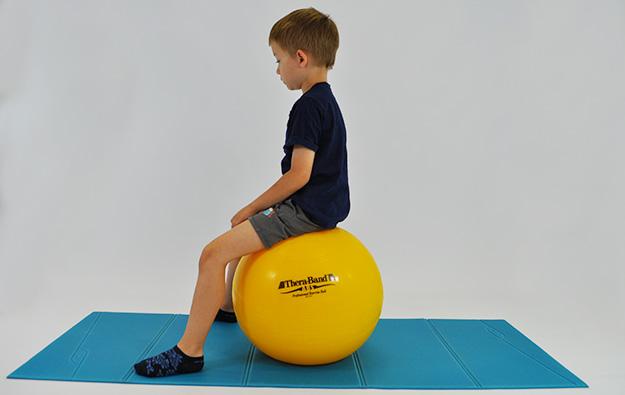 dziecko siedzi na dużej piłce