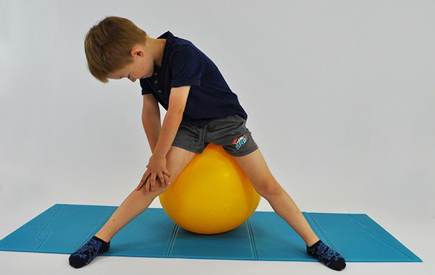 dziecko siedzi na dużej piłce w rozkroku, ręce jedna na drugiej na kolanie