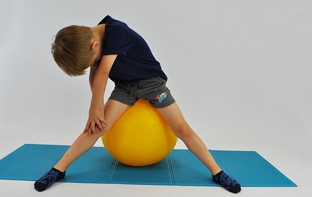 dziecko siedząc na dużej piłce w siadzie rozkrocznym wykonuje skłon w kierunku stopy, wytrzymuje 10-15 sekund i wraca do pozycji wyjściowej