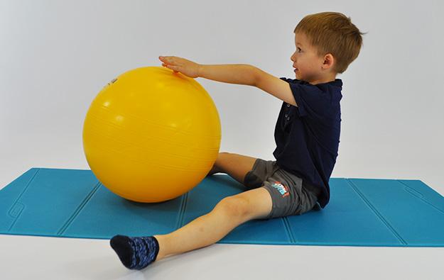 dziecko siedzi w siadzie rozkrocznym, tułów wyprostowany, piłka między nogami, ręce na piłce