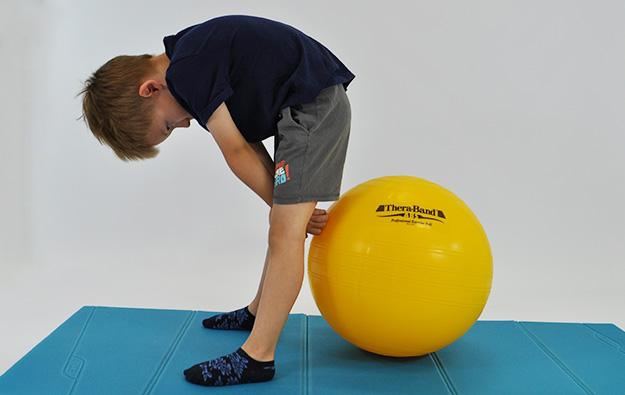 dziecko stoi przodem w rozkroku pochylone, z tyłu za jego nogami duża piłka