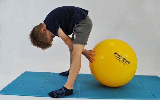 dziecko stoi przodem w rozkroku pochylone, z tyłu za jego nogami duża piłka, która przytrzymuje rekami i pcha od siebie jak najdalej