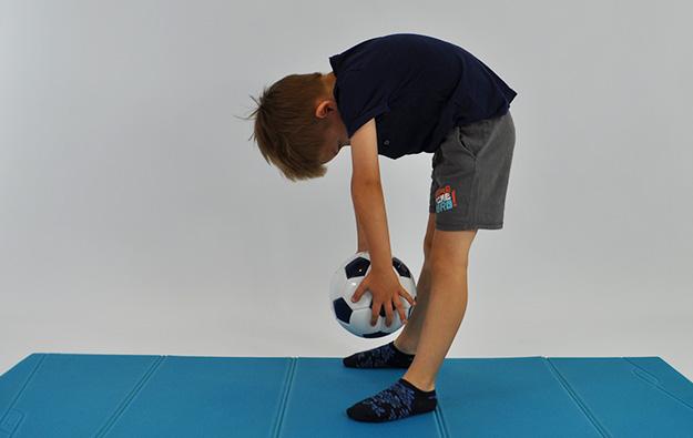 dziecko stoi w rozkroku, pochylone w przód w rekach trzyma piłkę