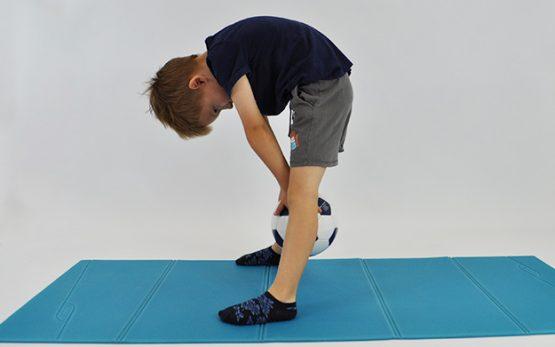 dziecko stoi w rozkroku, pochylone w przód w rekach trzyma piłkę, pcha piłkę między nogami jak najdalej w tył