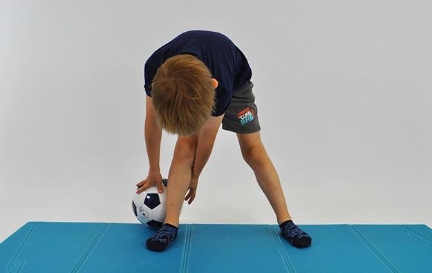 dziecko stoi w rozkroku pochylone w przód i trzyma piłkę wykonując nią ósemki wokół nóg