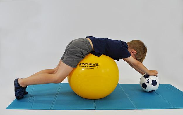 dziecko leży przodem na dużej piłce, kończyny górne zgięte w barkach dłonie oparte na małej piłce