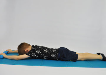 dziecko leży na brzuchu, czoło oparte, kończyny górne wyciągnięte w przód, w dłoniach trzyma ciężarki