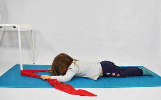 dziecko leży przodem, w rękach trzyma taśmę do ćwiczeń zaczepioną o nogę krzesła