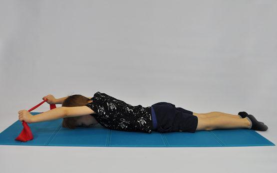 dziecko leży na brzuchu, czoło oparte, kończyny górne wyciągnięte w przód, w dłoniach trzyma taśmę elastyczną