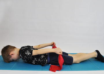 dziecko leży na brzuchu, czoło oparte, kończyny górne wzdłuż tułowia leżą na podłodze, w rękach taśma elastyczna