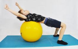 dziecko leży tyłem na piłce, ręce zgięte w barkach ułożone nad głową