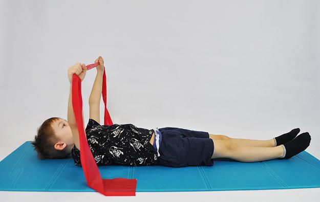 dziecko leży tyłem, ręce wyciągnięte w przód, w rękach trzyma taśmę do ćwiczeń