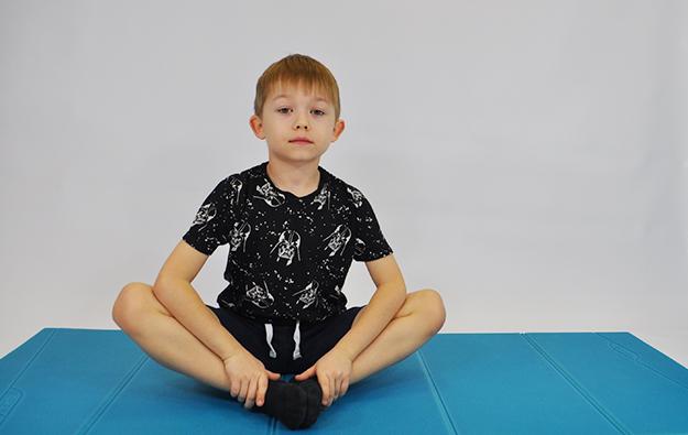 Poizometryczna relaksacja mięśni, siedzące dziecko na macie likwidujące nadmierne napięcie mięśni