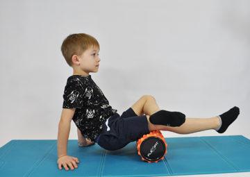 dziecko siedzi i roluje mięśnie