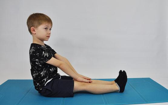 ćwiczenie rozciągające mięśnie kulszowo-goleniowe. Dziecko w siadzie prostym prostuje kolana