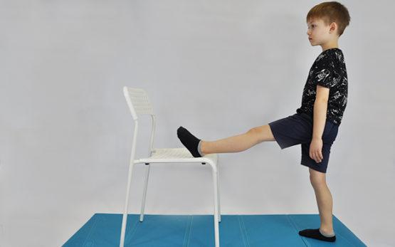 ćwiczenie rozciągające mięśnie kulszowo-goleniowe. Dziecko stoi, jedna noga wyprostowana, stopa oparta na krześle. Dziecko pochyla tułów w przód.