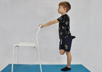 ćwiczenie rozciągające mięsień prosty uda. Dziecko stoi przodem do krzesła. Prawa ręka trzyma oparcie krzesła, lewą ręką przyciąga zgiętą piętę do pośladka rozciągając przednią stronę uda.