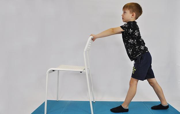 ćwiczenie rozciągające mięśnie łydek. Dziecko stoi przodem do krzesła (ściany stołu), lewa noga z przodu ugięta w kolanie, prawa z tyłu wyprostowana. Dziecko przenosi ciężar ciała na lewą nogę rozciągając prawą łydkę i nie odrywając jej od podłogi.