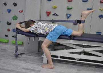 ćwiczenie rozciągające mięsień prosty uda. Dziecko leży na łóżku, lewa noga poza łóżkiem stopa całą podeszwą oparta na podłodze. Prawa noga ugięta w kolanie. Wokół kostki zawiązana taśma, której drugi koniec dziecko trzyma rękami nad głową.
